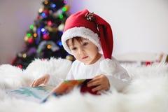Netter entzückender Junge, der ein Buch vor dem Weihnachtsbaum liest Stockbild