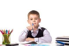 Netter erfüllter durchdachter lächelnder Schüler, der am Schreibtisch auf dem weißen Hintergrund sitzt stockbild
