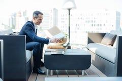 Netter erfolgreicher Geschäftsmann, der einen Ordner mit Dokumenten hält Lizenzfreie Stockfotografie