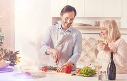 Netter erwachsener Mann, der mit seiner gealterten Mutter kocht stockfoto