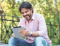 Netter erwachsener Mann, der seine digitale Tablette hält und in den Park surft Stockfoto