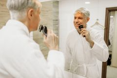 Netter erwachsener Mann rasiert sich am Spiegel im Badezimmer lizenzfreie stockbilder