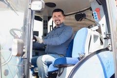 Netter Fahrer, der in der großen Feldmaschine sitzt Stockfotografie