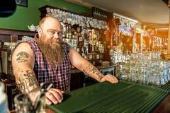 Netter fetter Tapster, der im Alkoholiker arbeitet Stockfotografie