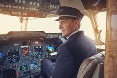 Netter Flieger, der im Cockpit aufstellt lizenzfreie stockbilder
