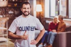 Netter Freiwilliger, der sich seinen Daumen zeigt lizenzfreies stockfoto
