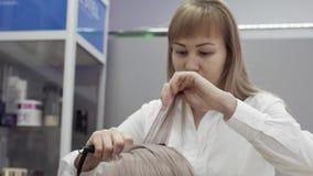 Netter Friseur der jungen Frau, der Frisur mit dem Bügeln Kundenmädchen antut stock video footage
