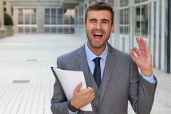 Netter Geschäftsmann, der ein OKAYzeichen blinzelt und gibt Stockbilder