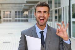 Netter Geschäftsmann, der ein OKAYzeichen blinzelt und gibt Lizenzfreies Stockfoto