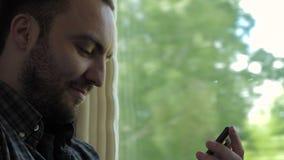 Netter Geschäftsmann empfängt gute Nachrichten an seinem Telefon beim Reisen in einen Zug stock video footage