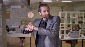 Netter Geschäftsmann mit Bart tanzt in das Büro und lächelt, Kollegen, aufpassen an ihm, bearbeiten Konzept, sich entspannen