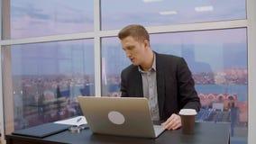 Netter Geschäftsmannanfangsarbeitstag bei Tisch mit Notizbuch-PC im Büro stock video footage