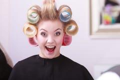 Netter glücklicher blonder Mädchenhaarlockenwickler-Rollenfriseur-Schönheitssalon Stockfotografie