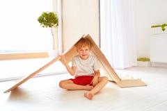 Netter glücklicher Junge, der mit Pappschachtel wie mit Spielzeughaus spielt Lizenzfreie Stockfotografie