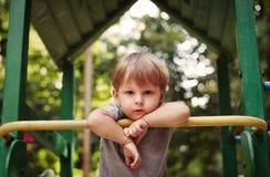 Netter glücklicher kleiner Junge, der auf einem Geländer sich lehnt Stockbilder
