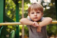 Netter glücklicher kleiner Junge, der auf einem Geländer sich lehnt Lizenzfreies Stockbild