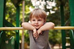 Netter glücklicher kleiner Junge, der auf einem Geländer sich lehnt Lizenzfreies Stockfoto