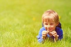 Netter glücklicher kleiner Junge, der im grünen Gras auf Frühling liegt Stockbilder