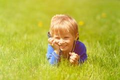 Netter glücklicher kleiner Junge, der im grünen Gras auf Frühling liegt Lizenzfreies Stockfoto