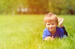 Netter glücklicher kleiner Junge, der im grünen Gras auf Frühling liegt Stockbild