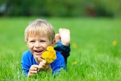 Netter glücklicher kleiner Junge, der im grünen Gras auf Frühling liegt Lizenzfreie Stockbilder