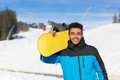 Netter glücklicher lächelnder Kerl hispanischer Mann-Griff Snowboard-Ski Resort Winter Snow Mountains Stockbilder