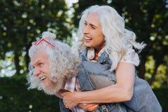 Netter glücklicher Mann, der seine Frau trägt stockbilder