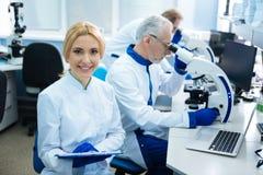 Netter glücklicher Wissenschaftler, der mit anderen im Labor arbeitet Lizenzfreie Stockbilder