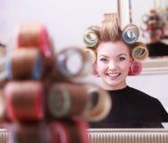 Netter glücklicher blonder Mädchenhaarlockenwickler-Rollenfriseur-Schönheitssalon Stockfotos