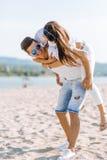 Netter gutaussehender Mann, der sein Freundindoppelpol trägt Lizenzfreies Stockbild