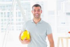 Netter Heimwerker, der Hardhat an der Baustelle hält Stockfoto