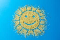 Netter Hintergrund Süßigkeiten besprühen Form der Sonne mit einem Lächeln Gelbe Zuckerkörner auf einer blauen Farbe stockfotografie