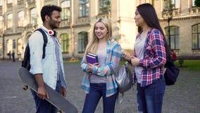 Netter hispanischer Mann, der mit Mädchen nahe College, Bruch, Freundschaft spricht lizenzfreie stockfotografie