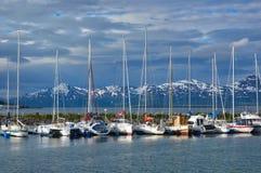 Netter im Stadtzentrum gelegener Jachthafen mit Schnee-mit einer Kappe bedeckten Bergen Stockbild