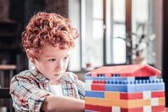 Netter intelligenter Junge, der ein Haus baut stockbilder