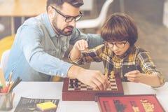 Netter intelligenter Mann, der seinen Sohn unterrichtet, Schach zu spielen stockbild