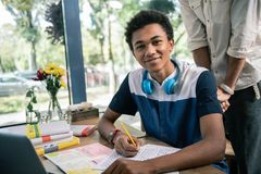 Netter intelligenter Student, der an der Aufgabe arbeitet stockfoto