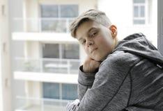 Netter Jugendlicher auf dem Fensterhintergrund Stockfotos