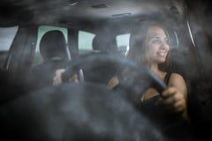 Netter Jugendlicher, der ihren Neuwagen fährt Stockfotografie