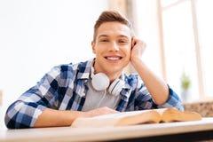 Netter Jugendlicher, der am Tisch mit einem Buch sitzt Stockfotografie