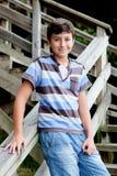 Netter jugendlicher Junge, der in der hölzernen Treppe lächelt Stockbild