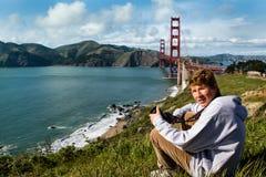 Netter Jugendlicher in San Francisco mit Golden gate bridge lizenzfreie stockbilder