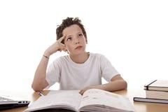 Netter Junge auf dem Schreibtisch studierend und denkend stockbilder