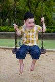 Netter Junge auf einem Schwingen Stockbild