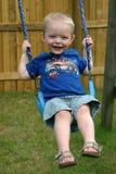 Netter Junge auf Schwingen stockfoto