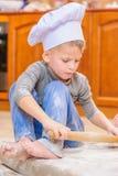 Netter Junge in Chef ` s Hüten, die auf dem Küchenboden beschmutzt mit Mehl sitzen, mit Lebensmittel spielen, Verwirrung machen u lizenzfreie stockfotografie