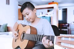 Netter Junge, der Akustikgitarre spielt Stockfoto