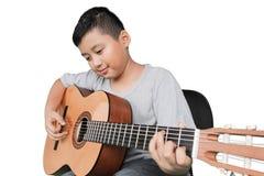 Netter Junge, der Akustikgitarre spielt Stockbild