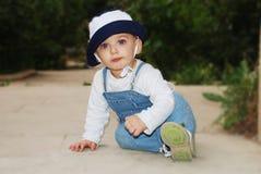 Netter Junge, der auf dem Fußboden sitzt Lizenzfreies Stockbild