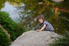 Netter Junge, der auf dem See spielt Lizenzfreie Stockbilder